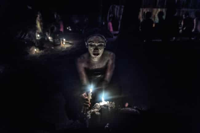Woman lights candle during iboga ceremony